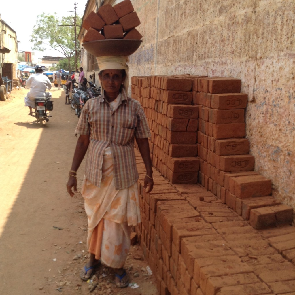 Building site worker carrying 8 bricks on her head back and forth all day in the scorching sun and ferocious heat.